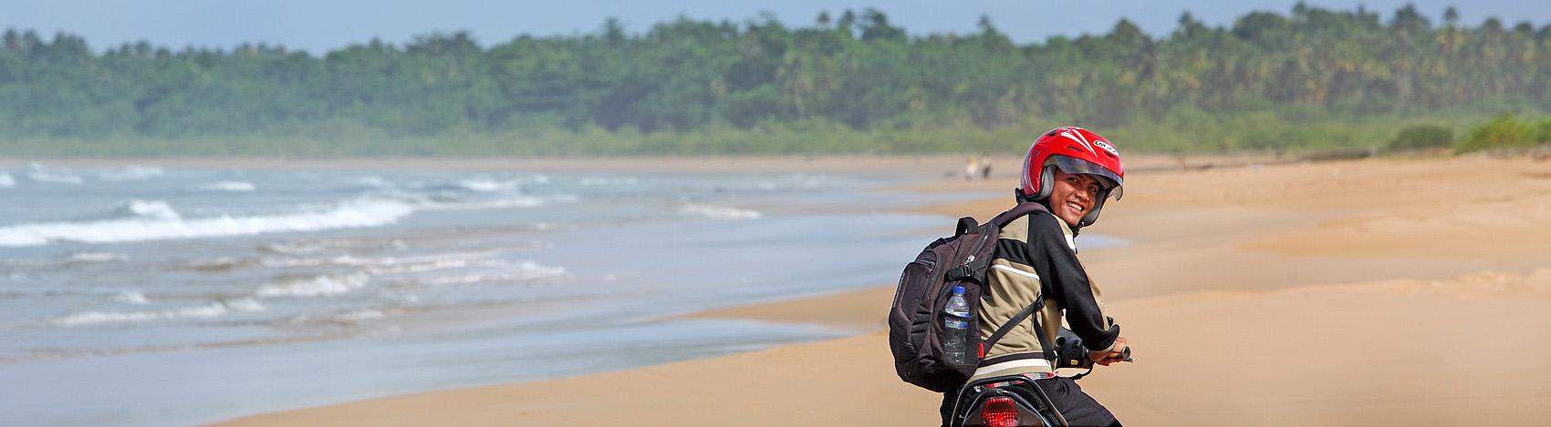 Motorbike touring on Toyalawa beach on the west-coast of North Nias (Nias Utara), Nias Island, Indonesia.