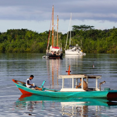 A local fishing boat passing two long-distance sailing boats in Lahewa lagoon, North Nias Regency.