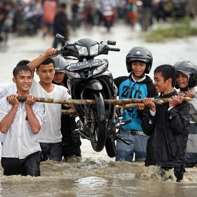 Team work; motorbikes being carried across a flooded section of the road to Lahewa. North Nias Regency.