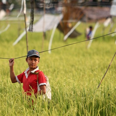 This girl is guarding a rice field against birds. Elaborate systems of strings and flags covers rice fields on Nias just before harvest time.