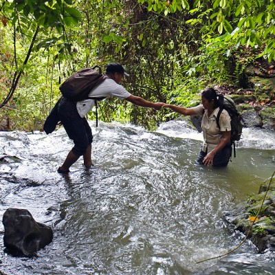 Ecotourism; crossing a stream during a trek to So'ora nasu waterfall, North Nias Regency (Nias Utara).