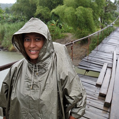 Shanti Fowler from the tourism office crossing Oyo river on a rainy day.